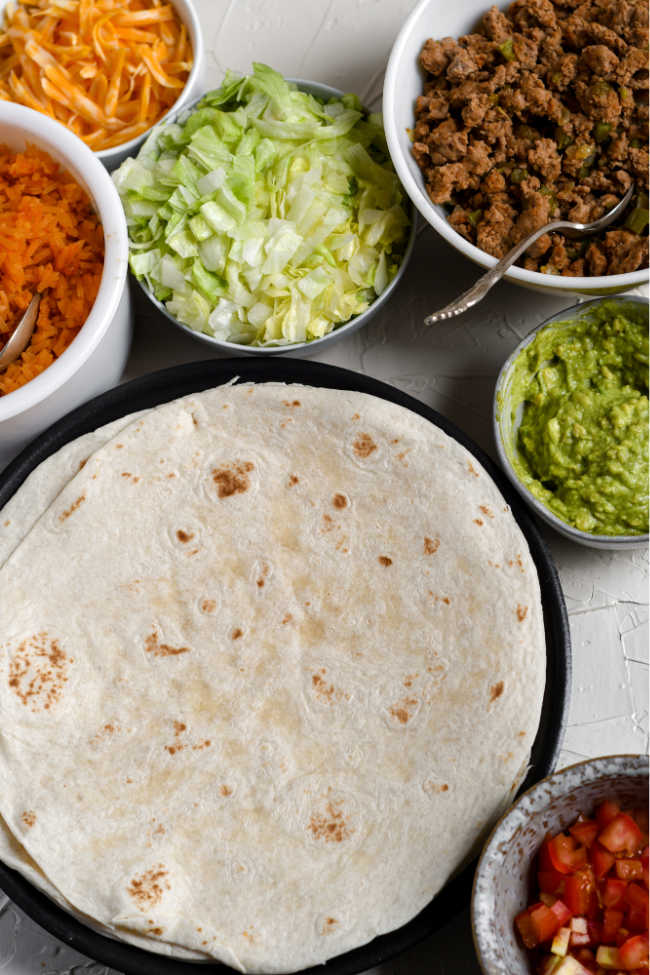 burrito fillings in bowls by tortillas, ready to be assembled