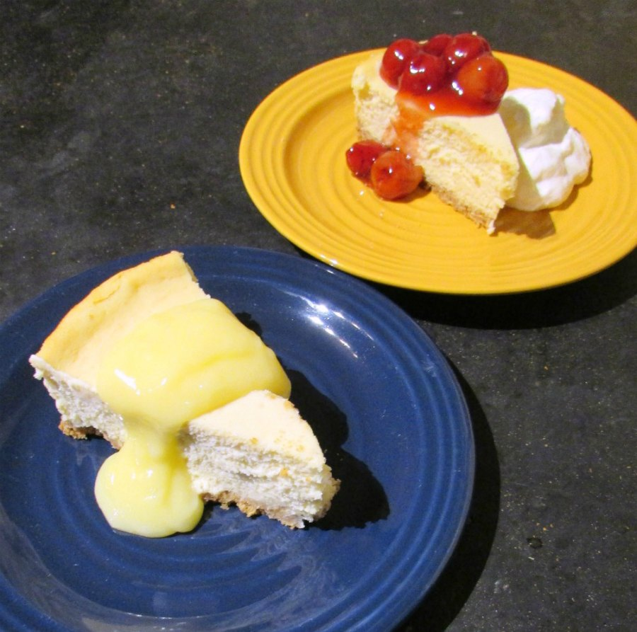 two slices of creamy sweetened condensed milk cheesecake one with lemon curd on top and the other with cherries and whipped cream.