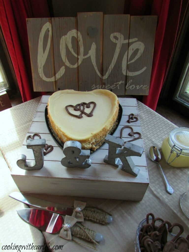 Heart shaped sweetened condensed milk cheesecake with chocolate hearts on top on wedding dessert table.