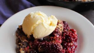 Serving of blackberry crisp with scoop of ice cream on top.
