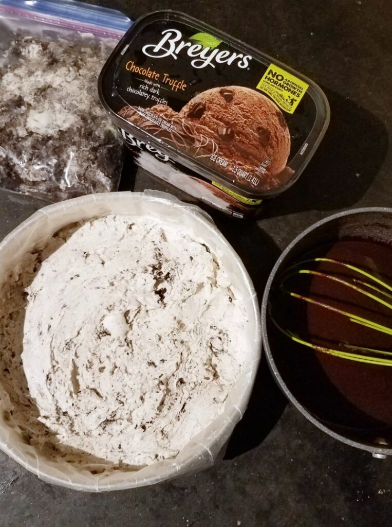 ice cream in pan with additional quart nearby along with pan of fudge sauce and bag of cookie crumbs.