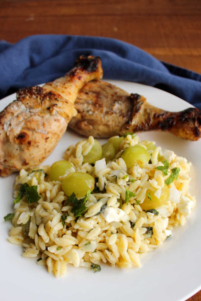 close up of sweet and savory pasta salad on plate with grilled chicken legs.