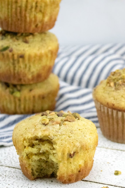 orange and pistachio muffins with bite missing