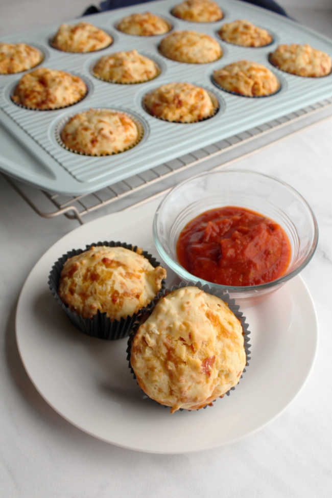 muffins on plate with pizza sauce with remaining muffins in cupcake tin in background