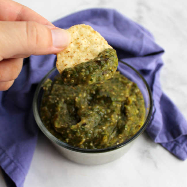 dipping chips into thick salsa verde