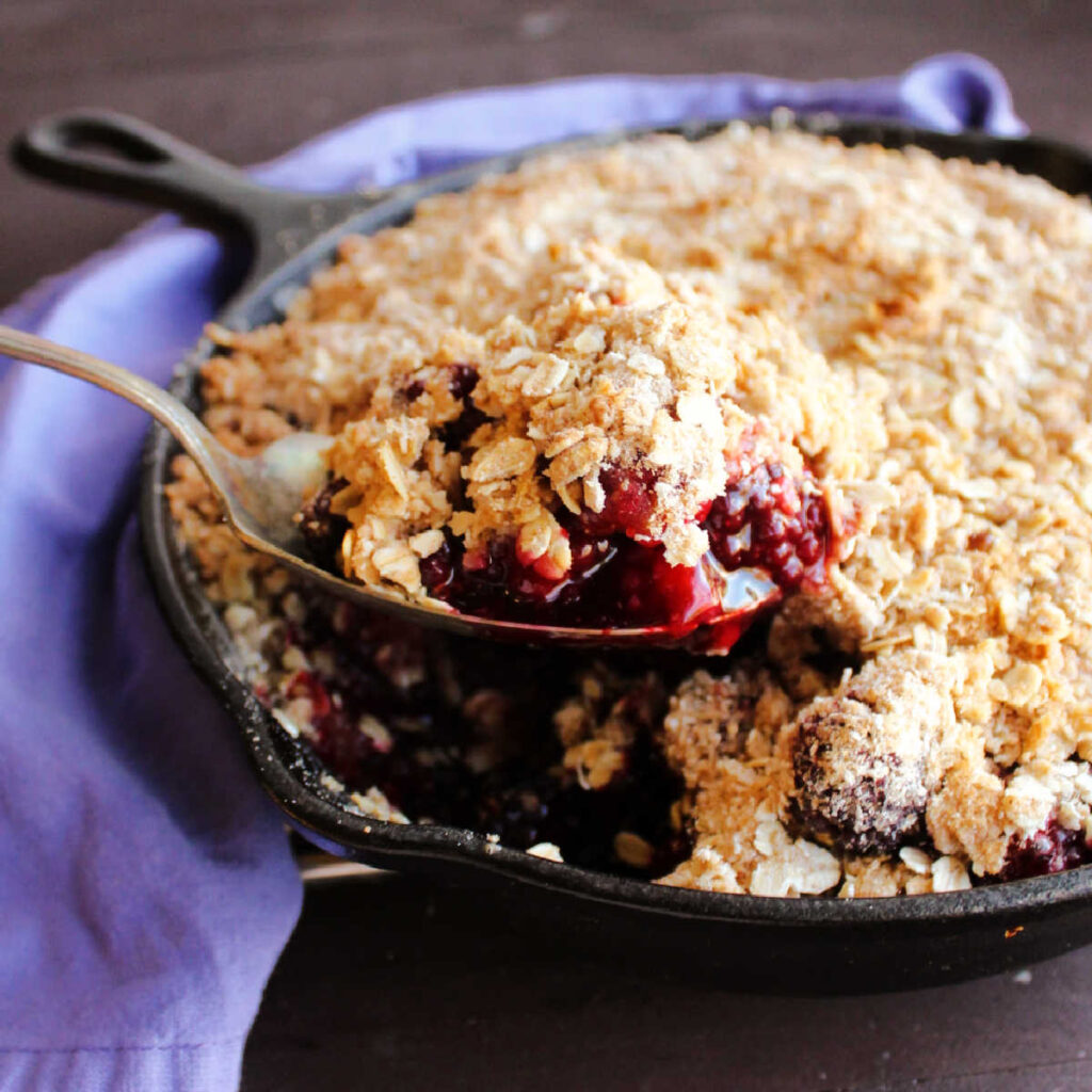 Spoon lifting out serving of blackberry crisp.