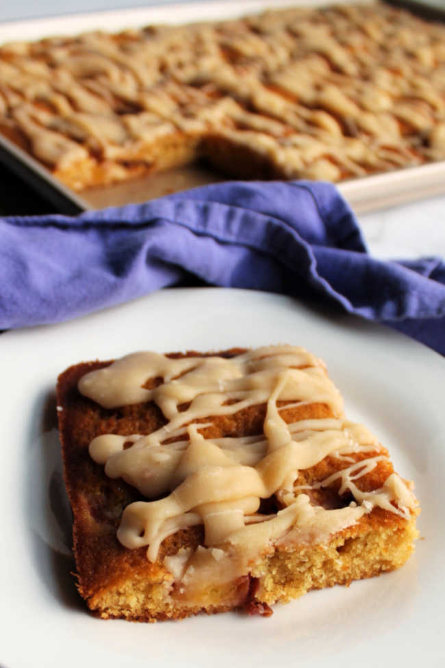 piece of brown sugar sheet cake topped with peaches and brown butter glaze.