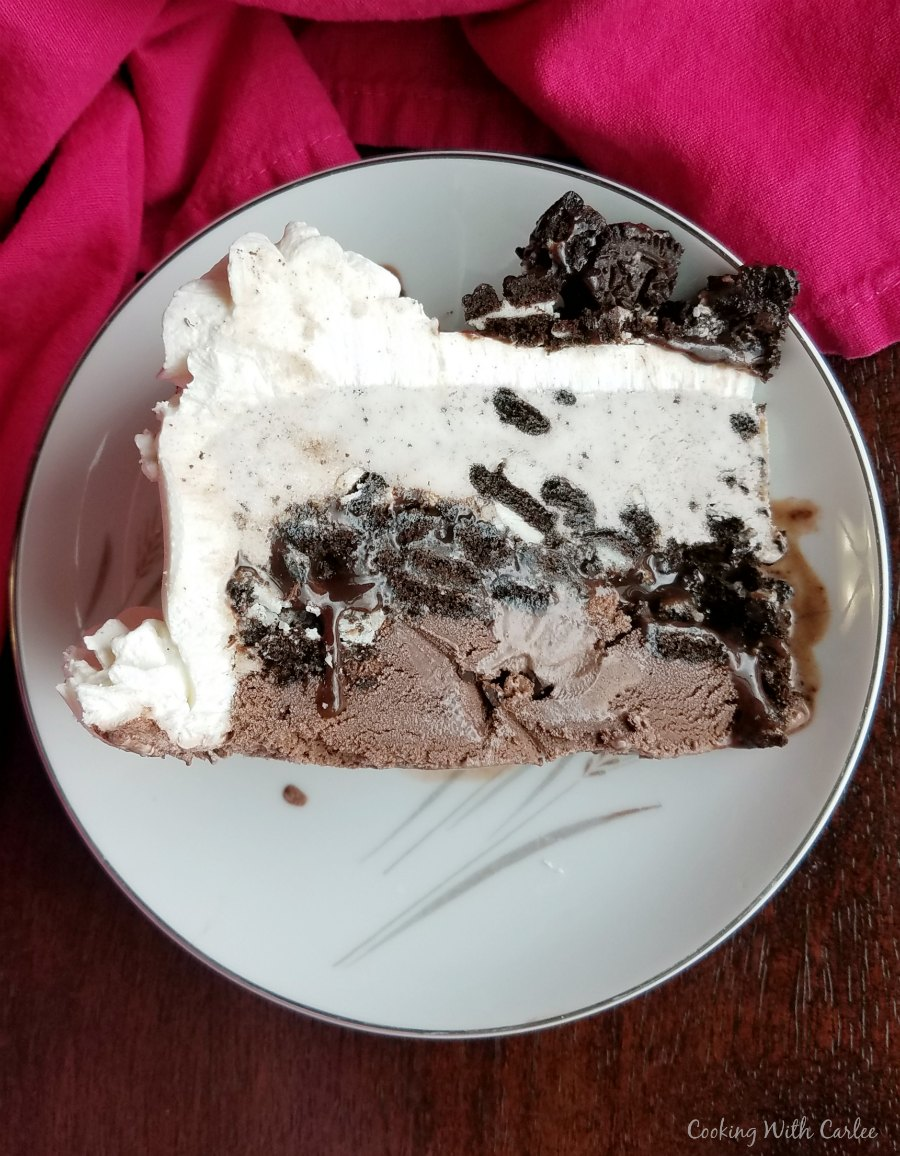 slice of ice cream cake with chocolate ice cream layer, fudge layer, white ice cream layer and cookie topping