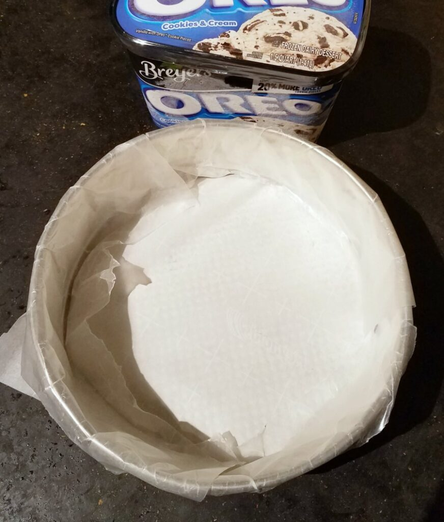 wax paper lined springform pan next to quart of ice cream.