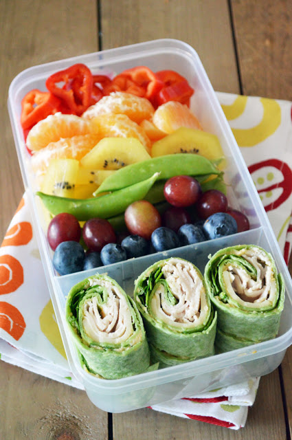 """We all know the saying, """"Eat a Rainbow!"""" and with this colorful bento box lunch, your kiddos will be! This rainbow lunchbox pairs a variety of fruits and veggies with simple pinwheels filled with hummus, turkey and spinach."""