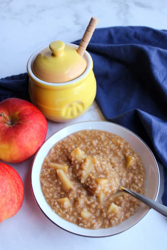 bowl of apple pie steel cut oats with honey and apples
