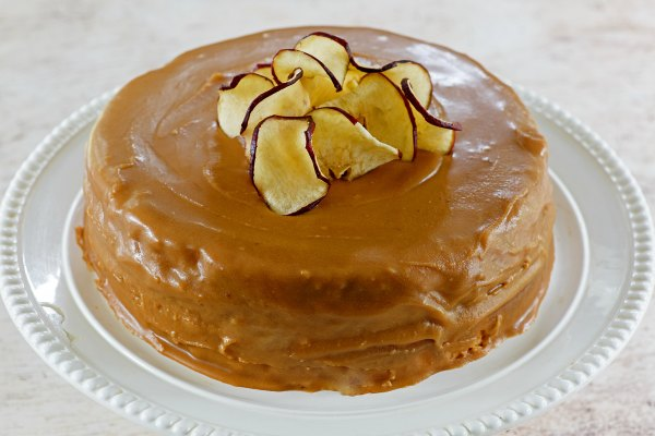 caramel frosted cake with pile of apple chips on top.