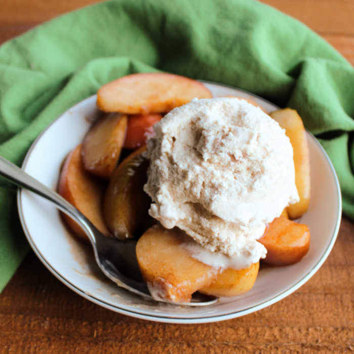 bowl of slow cooker cinnamon apples topped with scoop of homemade ice cream