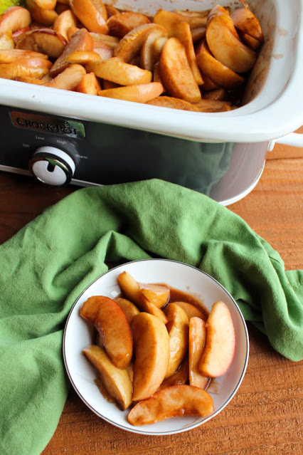 slow cooker filled with cooked apple slices with some served