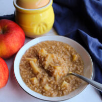 close bowl of steel cut oats with apple chunks next to honey jar and apples