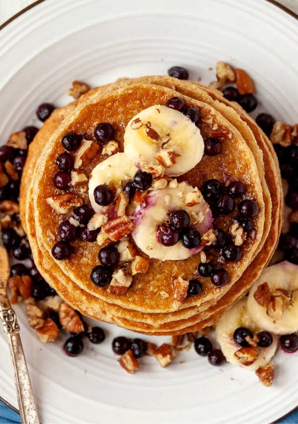 looking down on golden brown pancakes topped with fruit and nuts