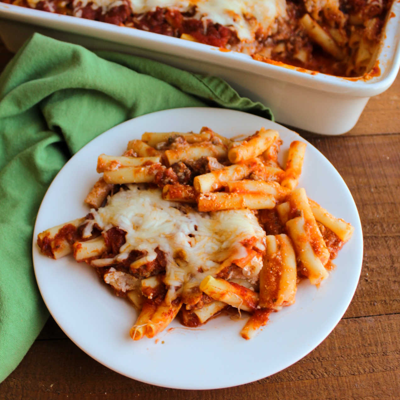 plate of cheesy baked ziti in front of casserole dish