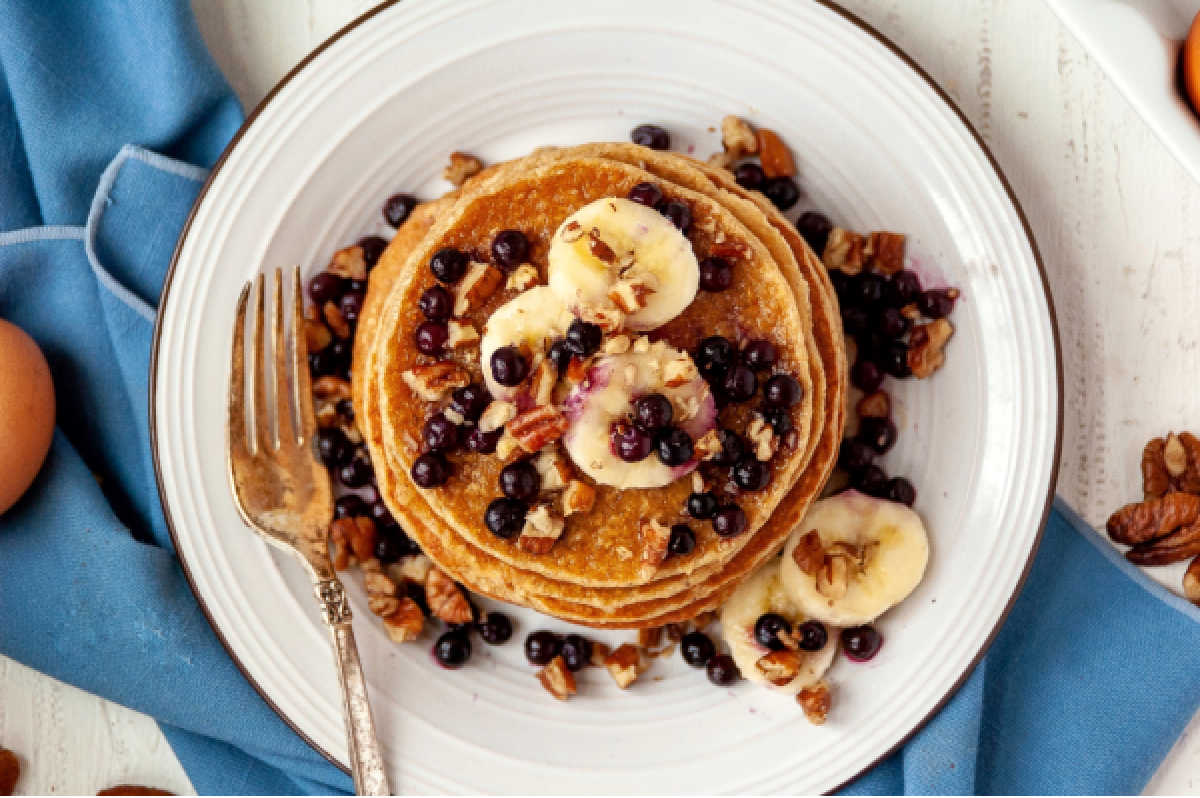 plate filled with berries, bananas and healthy blender pancakes