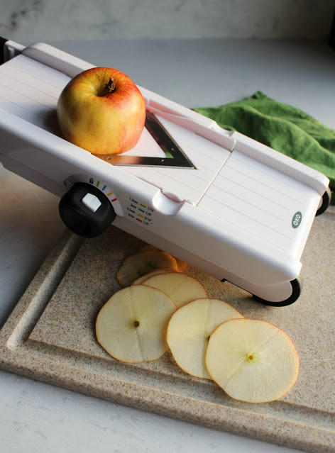 slicing apples thinly on mandolin to make apple chips
