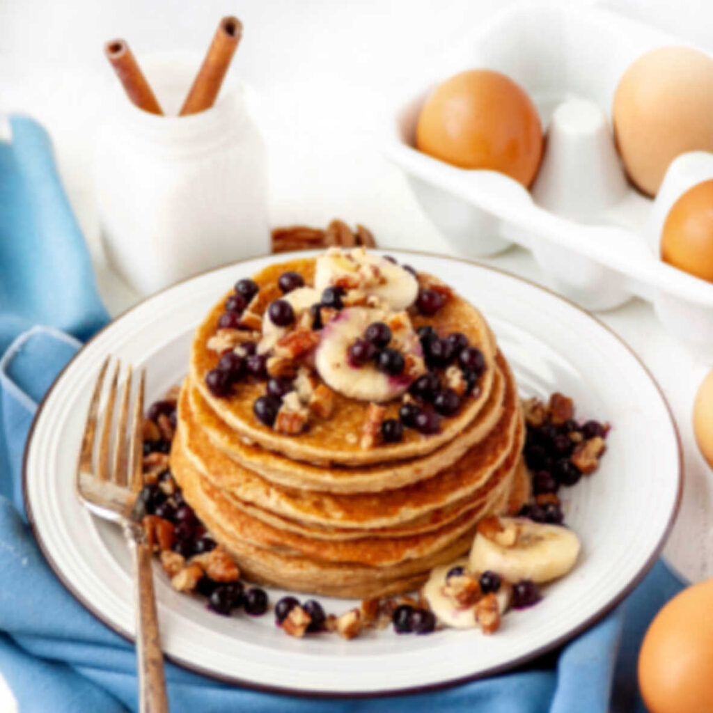 stack of pancakes topped with bananas, blueberries and pecans.