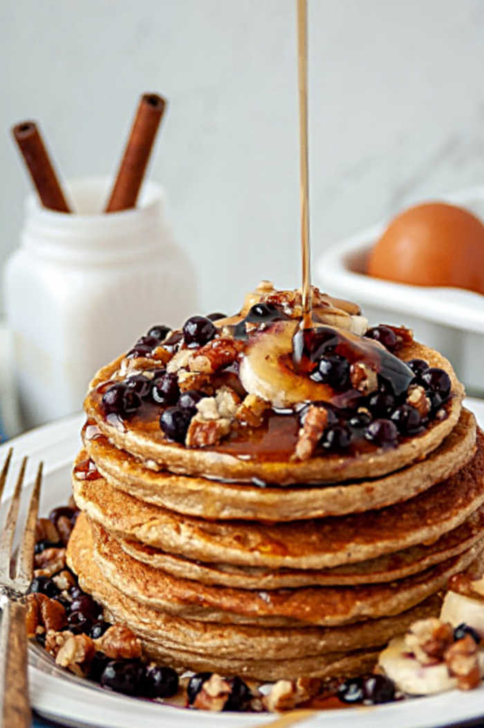 pouring syrup over stack of pancakes with fruit on top