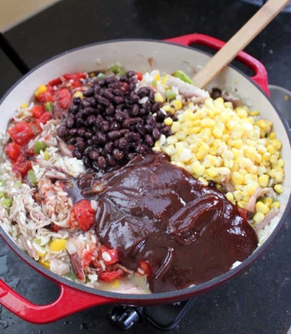 Adding black beans, corn and bbq sauce to skillet with rice and pulled pork mixture.