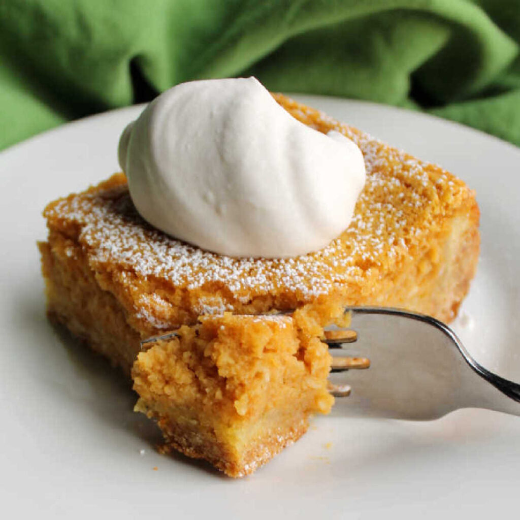 Fork going into piece of pumpkin gooey butter cake topped with maple whipped cream.
