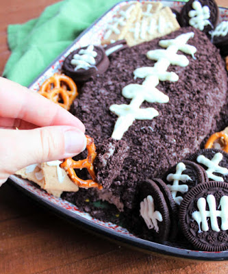 dipping pretzel into football shaped chocolate cheese ball