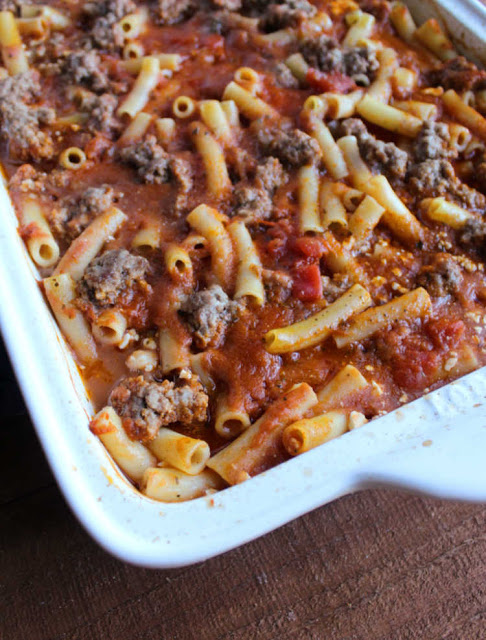 partially cooked baked ziti with pasta plumping up and ground beef looking cooked