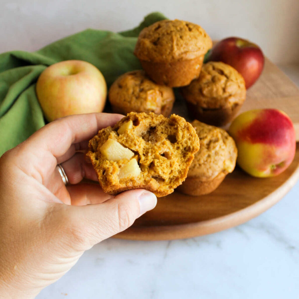 hand holding half a pumpkin muffin with chunks of apple inside.