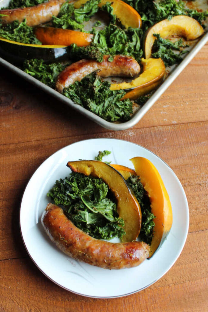 plate with sausage, kale and squash on it with sheet pan in background