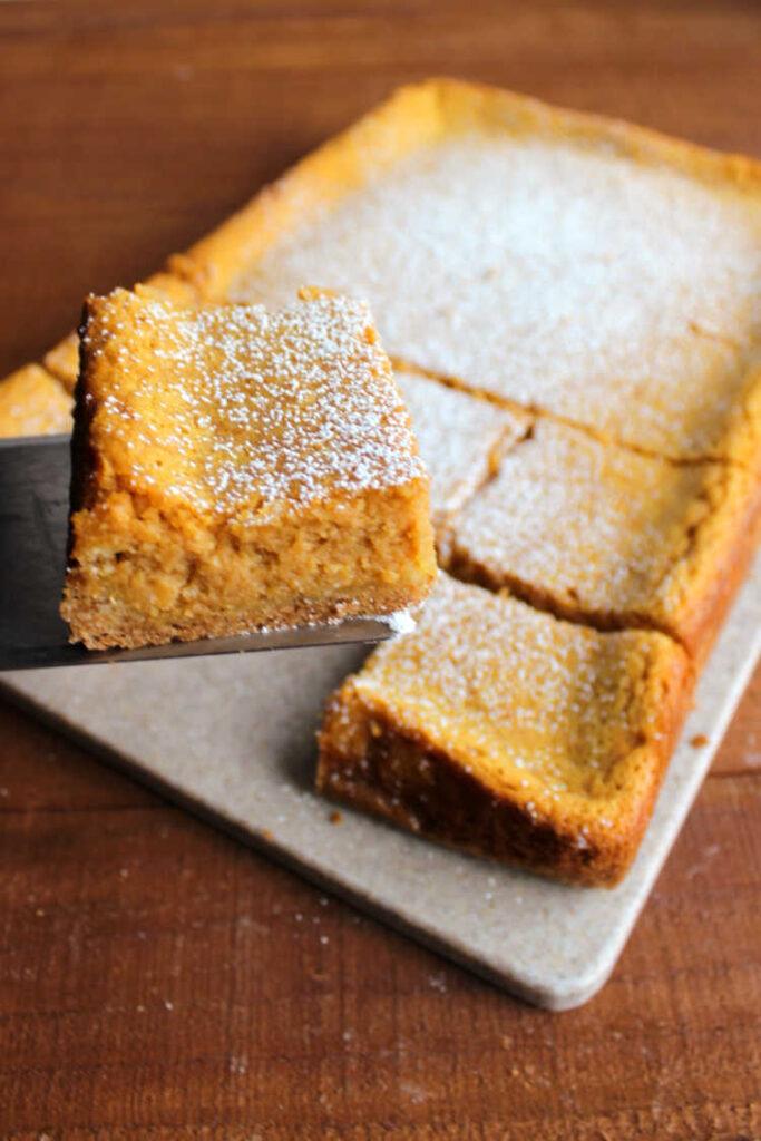 lifting square of cream cheese and pumpkin cake bars