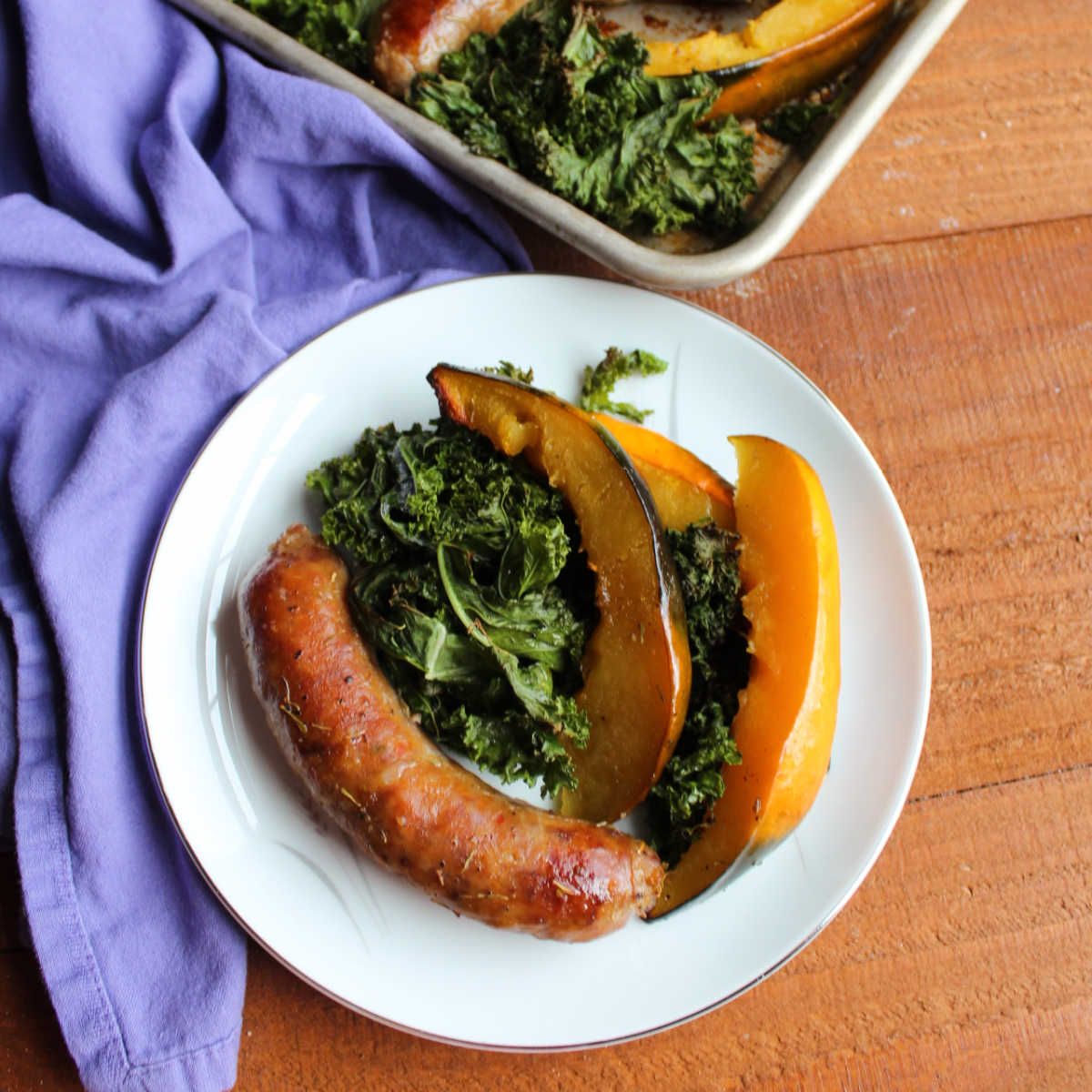 plate of roasted Italian sausage, acorn squash and kale ready to eat
