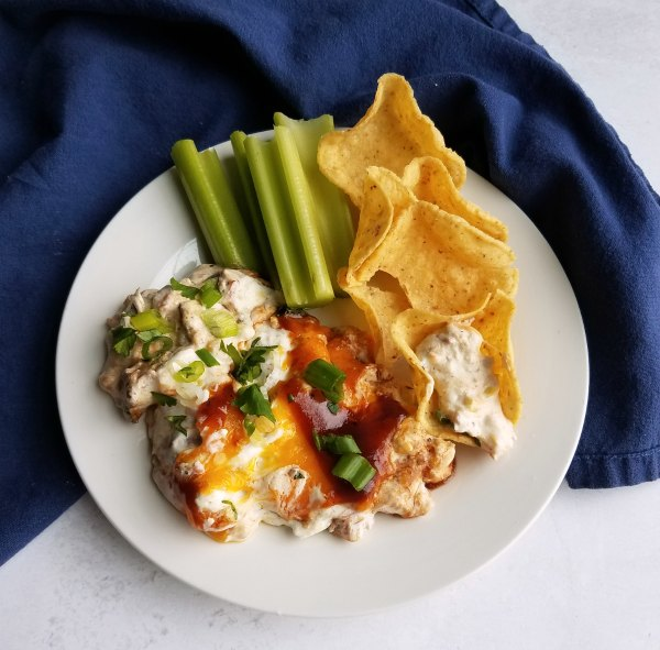 small plate filled with creamy pulled pork dip, tortilla chips and celery sticks.