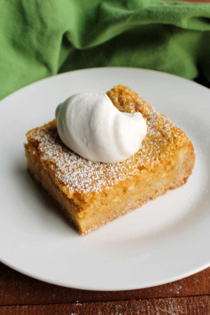 slice of pumpkin gooey butter cake with maple whipped cream.