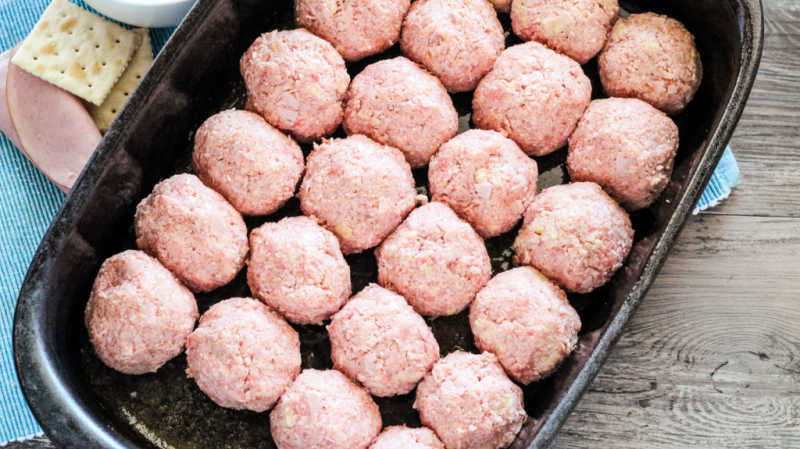 pan filled with pink raw ham balls ready to go in the oven.