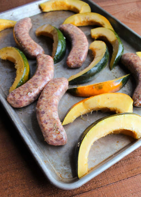 Italian sausage links and slices of acorn squash on sheet pan ready to go in oven