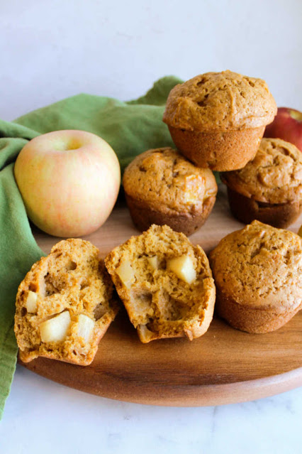 stack of pumpkin muffins with one broken open to show apple chunks inside