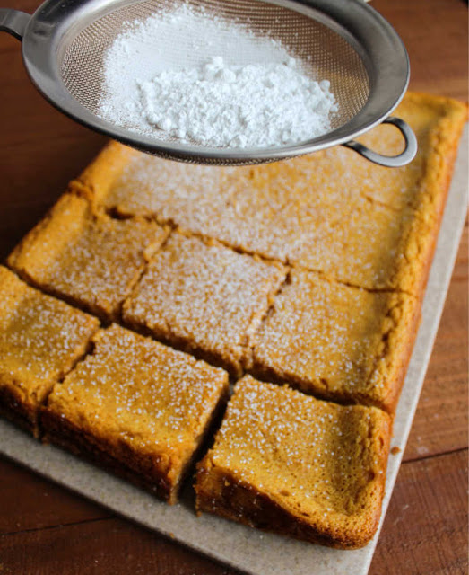 dusting powdered sugar over gooey pumpkin bars