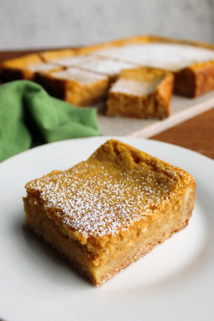 powdered sugar dusted pumpkin gooey butter cake bar on plate ready to eat.