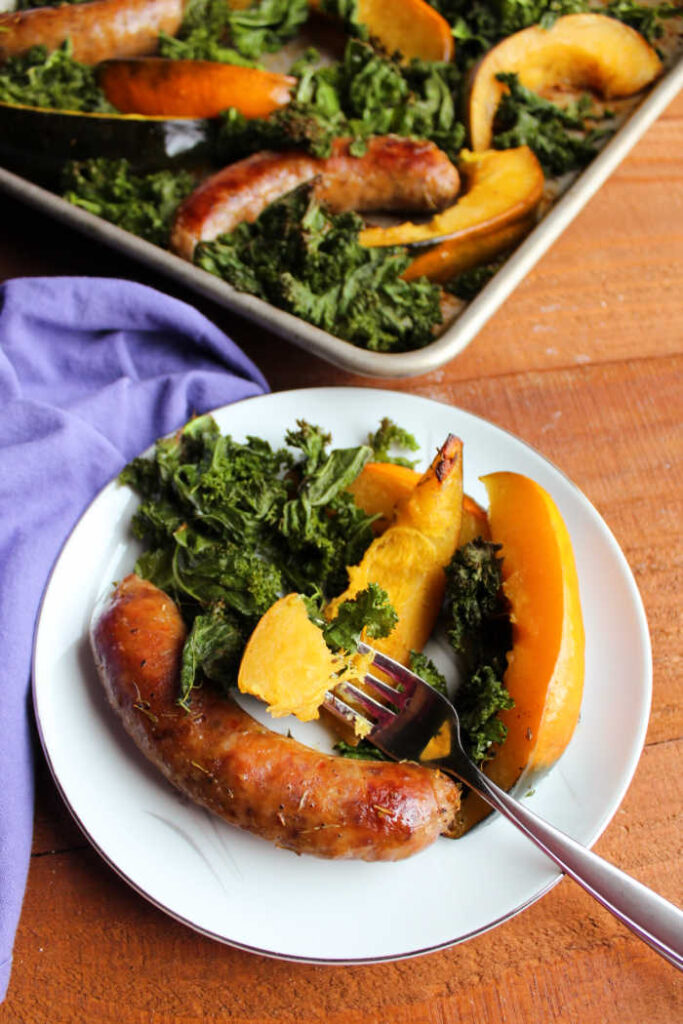 bite of tender acorn squash on fork with plate of kale and sausage