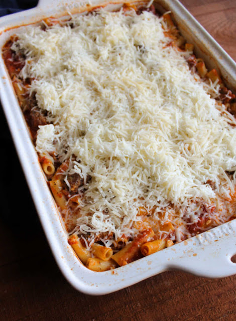 baked ziti topped with shredded cheese ready to go back into the oven