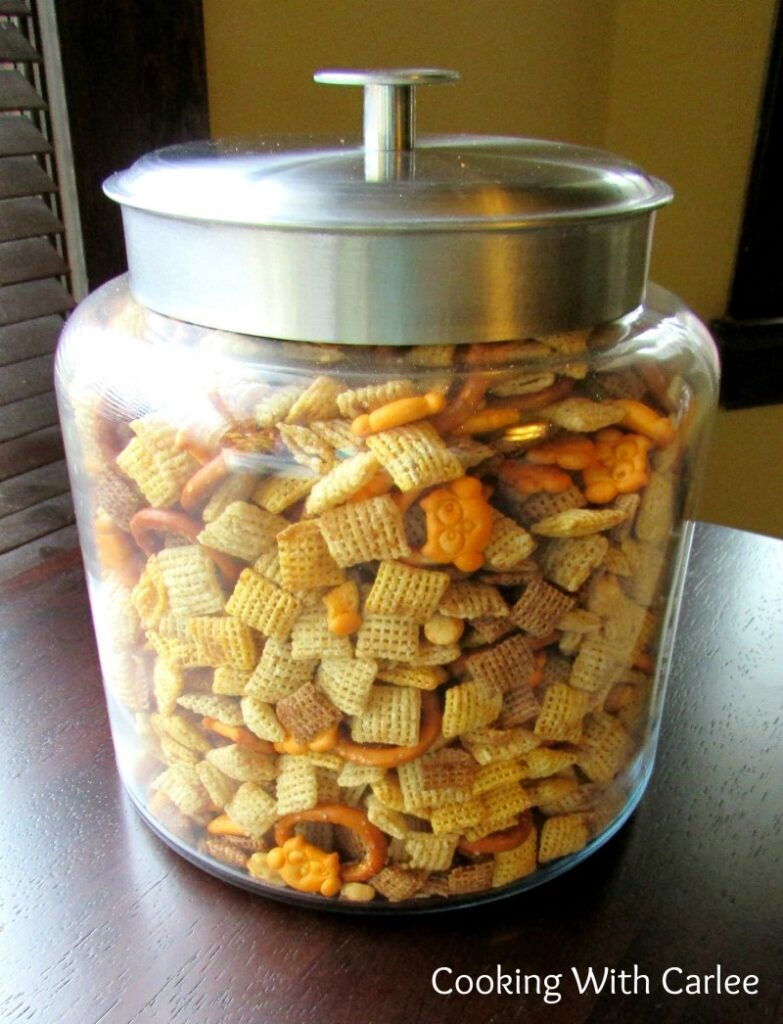 Jar of crunchy chex mix with a variety of cereals, cheese crackers, peanuts and more.