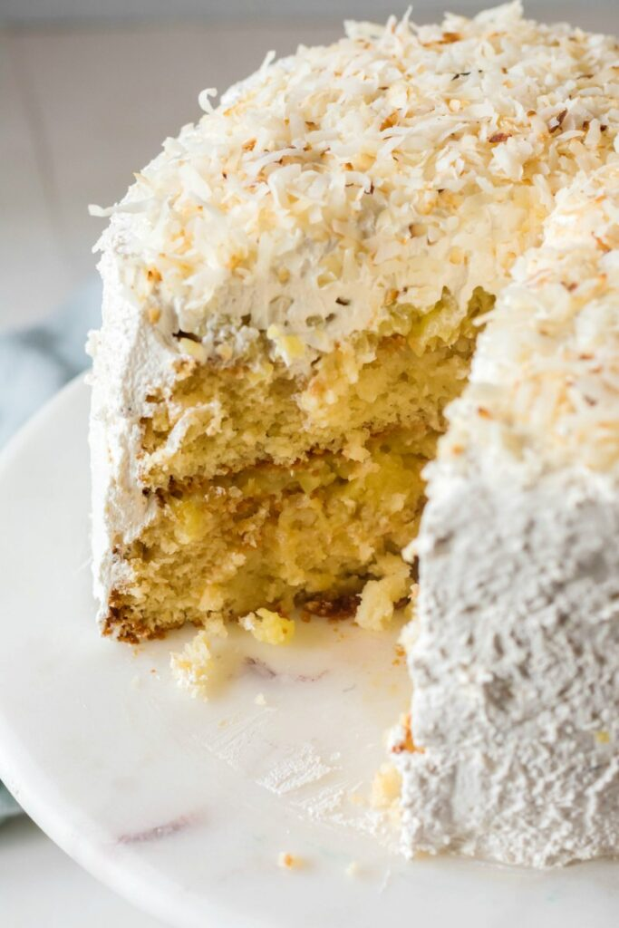 haleakala cake with layers of white cake, pineapple filling, Italian meringue frosting and coconut.