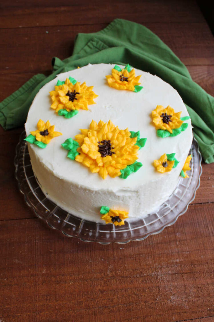 layer cake with 3D frosting sunflowers on top.