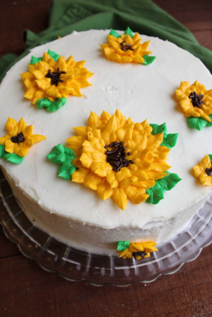 cake frosted in white buttercream with frosting sunflowers piped on top.
