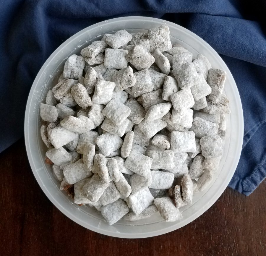bowl of powdered sugar coated chocolate and peanut butter muddy buddies