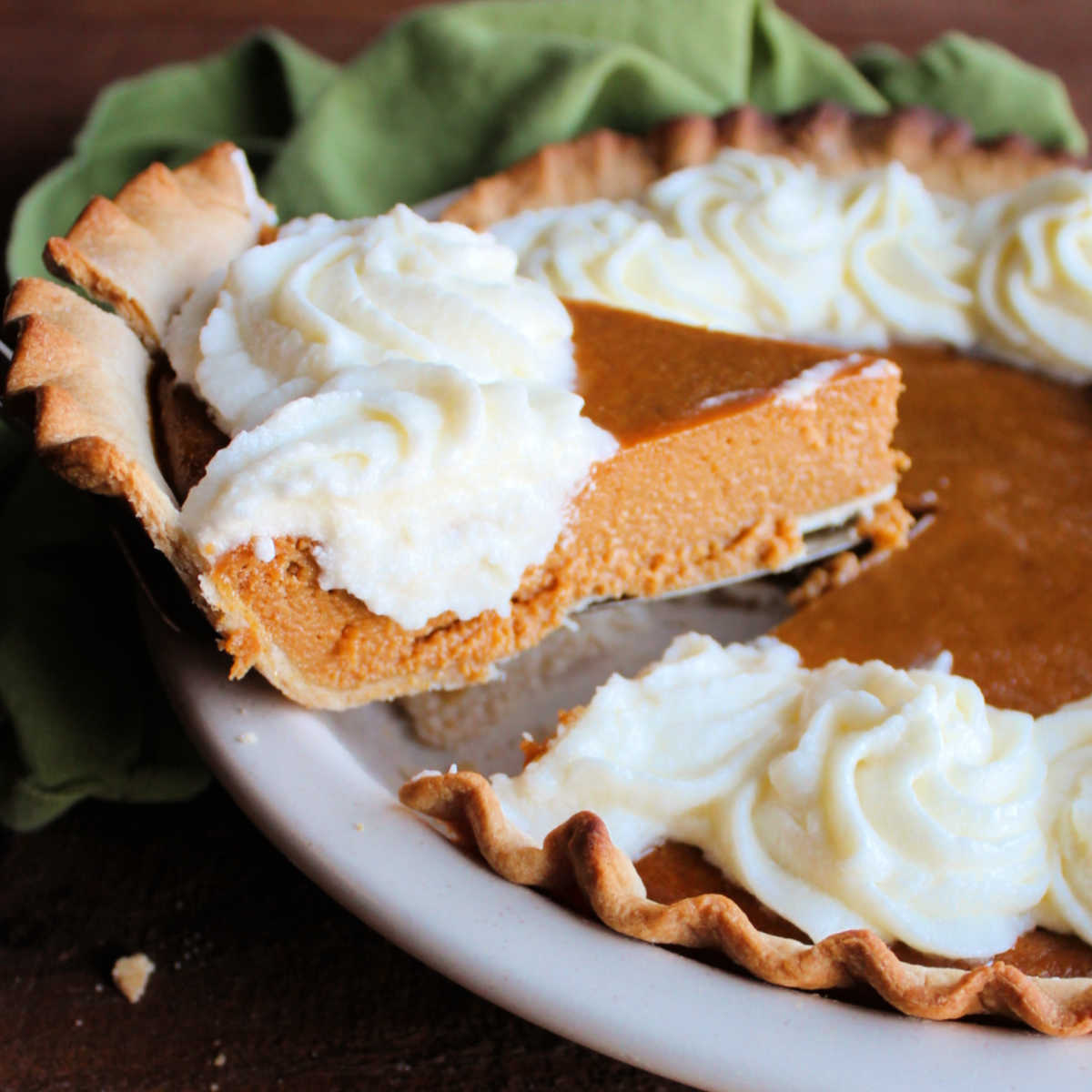 slice of whipped cream topped pumpkin pie being lifted out of pan