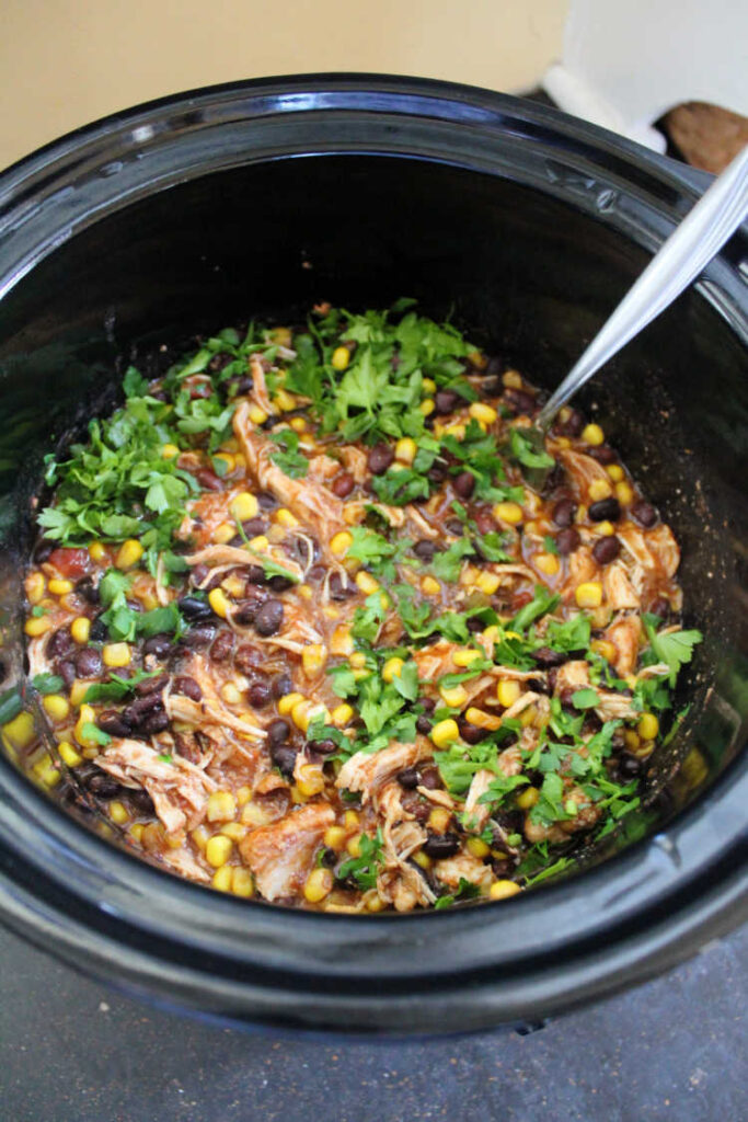 crock pot full of cooked shredded salsa chicken with black beans, corn and cilantro.