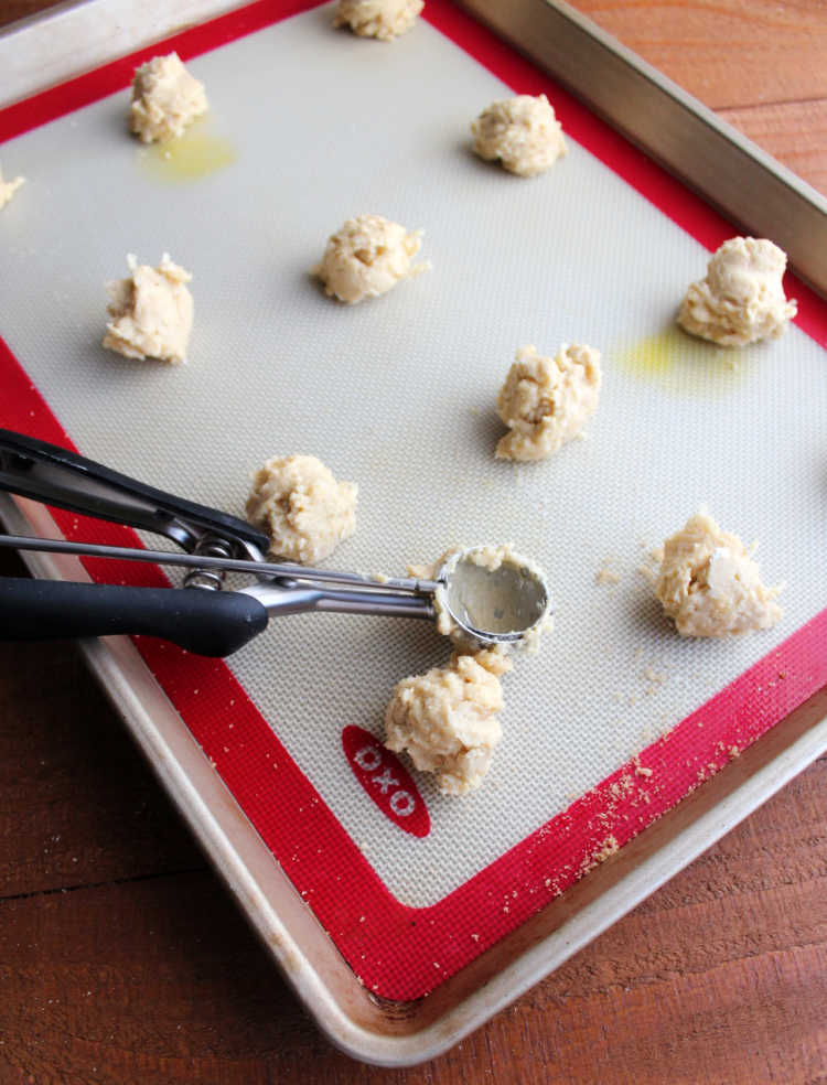 scooping small scoops of cuppa cookie dough onto silicone mat lined baking tray.
